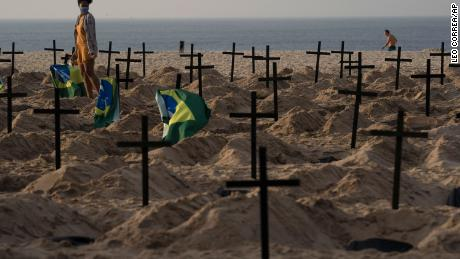 A woman walks amid symbolic graves on Rio de Janeiro's Copacabana beach. They were dug by activists protesting the government's handling of the Covid-19 pandemic.