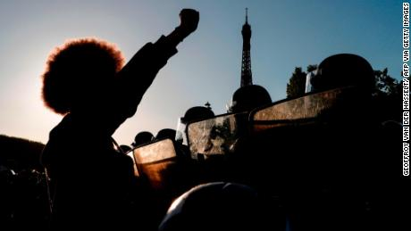 "People raise their fists in front of riot policemen during a protest at the Champ de Mars in Paris, with the Eiffel Tower in the background as part of worldwide ""Black Lives Matter"" protests in the wake of the death of George Floyd,"