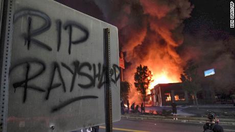 A Wendy's restaurant, background, burns Saturday in Atlanta.