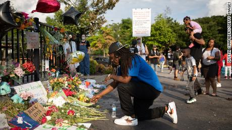 A mourner visits a memorial Sunday for Rayshard Brooks, who was shot in the back by police.