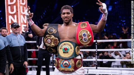 Joshua poses for a photo with the IBF, WBA, WBO & IBO World heavyweight title belts after beating Andy Ruiz Jr.