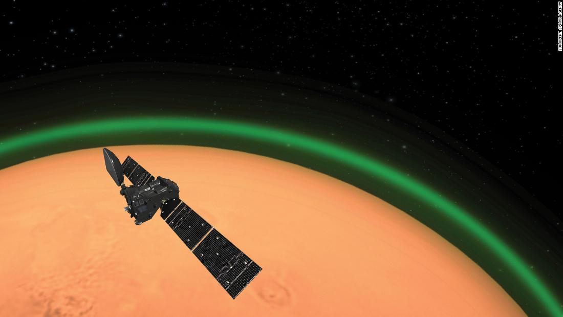 This artist's illustration shows the ExoMars Trace Gas Orbiter as it orbits Mars. The orbiter detected a layer of glowing green oxygen in Mars' atmosfera.