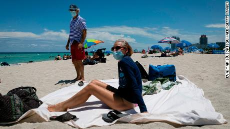 Diane, a nurse from Houston, Texas, sunbathes at the beach next to her husband, both wearing facemasks, in Miami Beach, Florida.