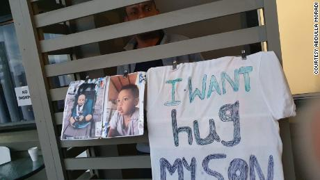 Saif Ali Saif peers out from his hotel room balcony where he has hung images of his three-year-old son.