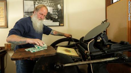 Loren Ackerman prints wooden money on an 1890s-era press in Tenino, Washington