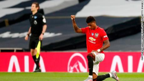 Manchester United striker Marcus Rashford takes a knee.