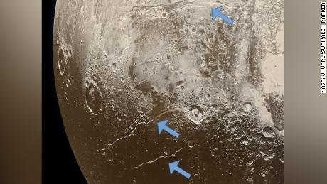 Extensional faults (indicated by arrows) on the surface of Pluto reveal expansion of the dwarf planet's icy crust. This was likely caused by the slow freezing of an ocean beneath the crust.