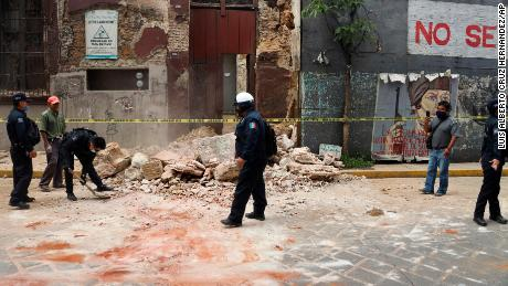 A policeman removes rubble from a building damaged by the earthquake in Oaxaca, Mexico.