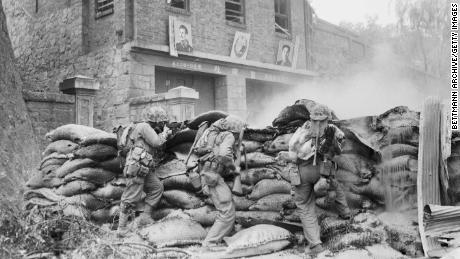 US Marines take cover behind a barricade as street fighting rages in Pyongyang. On the wall in the background are images of Soviet leader Joseph Stalin and North Korean leader Kim Il Sung.