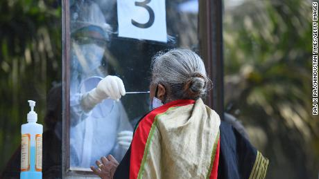 A medic collects a swab from a woman to test for Covid-19 on June 18 in New Delhi, India.
