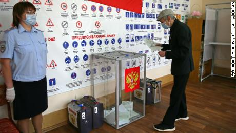 A man casts his vote at a ballot box in the village of Lugovoye.