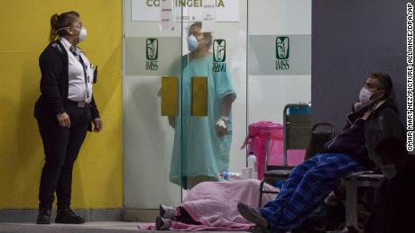 People wearing face masks wait outside an emergency room in Tijuana to be tested for coronavirus in April.