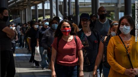 Commuters line up to cross to the United States at the San Ysidro crossing port in Tijuana on June 16, 2020.