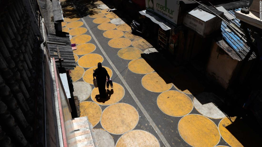 A woman walks along a road painted with circles to help people maintain social distancing in Mumbai, India, a giugno 29.