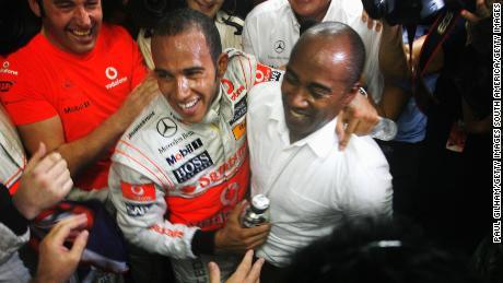 Hamilton celebra con su padre Anthony Hamilton (R) en el garaje de su equipo tras el Gran Premio de Brasil en el Circuito de Interlagos el 2 de noviembre de 2008 en Sao Paulo, Brasil.