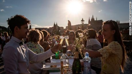 People dine at a communal table stretching across the Charles Bridge in Prague after coronavirus restrictions were eased on June 30, 2020.