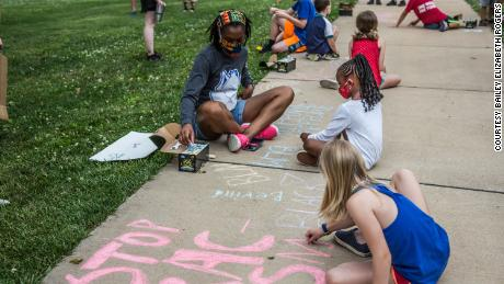 """Children writing phrases """"Stop Racism"""" and """"Black Lives Matter"""" on the sidewalk with chalk during the march."""