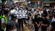 """Passers-by and protesters gather in Causeway Bay, Hong Kong. A protester is seen carrying a flag that says """"Liberate Hong Kong, revolution of our times,"""" an act that could now be considered a crime under the city's new national security law."""
