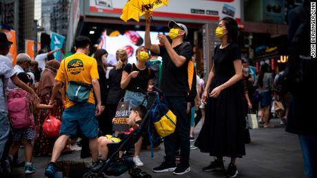 A family in Causeway Bay is seen with signs and yellow paraphernalia, the color of the pro-democracy movement.