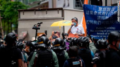 Former lawmaker and longtime activist Lee Cheuk-Yan is seen addressing a crowd in Causeway Bay as riot police stand in the background. He was arrested soon after.