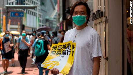District Councilor and barrister Lawrence Lau holds up a poster in the Hong Kong district of Causeway Bay, shortly before police started clearing the area, on Wednesday.