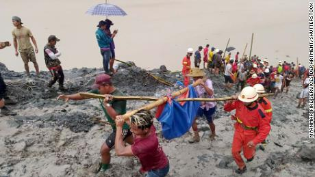 Rescue workers carrying the body of a victim after a landslide at a jade mining site in Myanmar