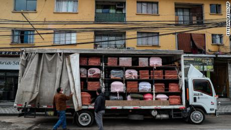 Bergut Funeral Services employees deliver coffins to a funeral store in Santiago, Chile, on June 19, 2020. Coffin production has increased 120%, according to owner Nicolas Bergerie.