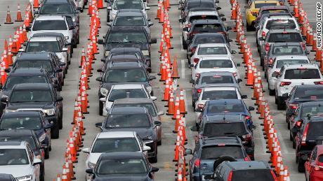 Cars wait at a drive-through coronavirus testing site Sunday in Miami Gardens.