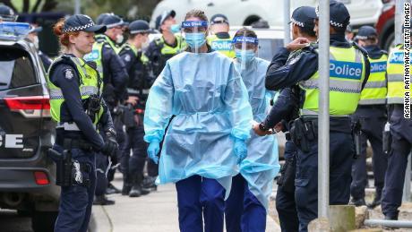 Medical staff wearing PPE walk into the Flemington public housing flats on July 5 in Melbourne, Australia after nine public housing estates were locked down.