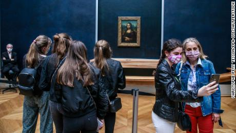 Visitors wearing face masks take photographs in front of the Mona Lisa at the Louvre Museum in Paris on July 6.