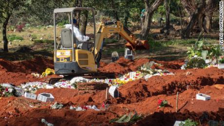 A backhoe has been brought in to dig more graves at the Vila Formosa cemetery in São Paulo.