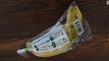 A single banana is swaddled tightly plastic wrapping.