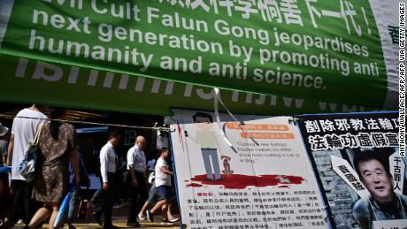 Pedestrians walk past banners criticising the Falun Gong spiritual movement displayed along a pavement in Causeway Bay, a popular shopping district, in Hong Kong on April 25, 2019.