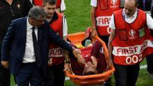 Cristiano Ronaldo este mângâiat de antrenorul Portugaliei, Fernando Santos, în timp ce este transportat pe o targă în afara terenului în finala Euro 2016.