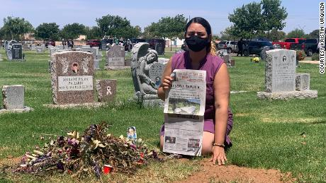 Kristin Urquiza hold her father's obituary over his grave.