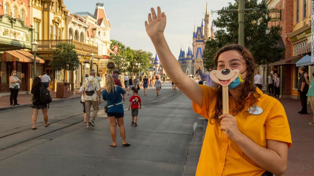 "In this handout photo provided by the Walt Disney World Resort, a worker welcomes guests to the Magic Kingdom Park in Lake Buena Vista, Florida, a luglio 11. <a href =""https://www.cnn.com/travel/article/disney-masks-covid-rides-trnd/index.html"" target =""_blank&ampquott;>The park's reopening</un> came the same weekend that Florida reached a record high for single-day case count increase."