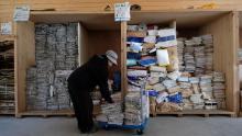 Un muncitor sortează ziare și reviste pentru reciclare la un centru de reciclare Kamikatsu.