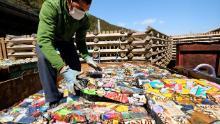 Un rezident stive foi de cutii de aluminiu compactate la un centru de reciclare din Kamikatsu, Prefectura Tokushima.