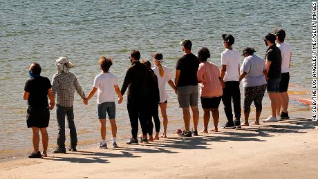 "Friends and former castmates held hands and shouted ""Say her name -- Naya,"" as they gathered at Lake Piru on Monday morning."