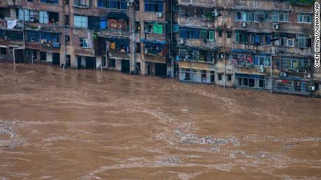 Las inundaciones fluyen más allá de un edificio residencial en Chongqing en el suroeste de China el 1 de julio.