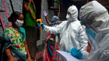 Medical volunteers wearing Personal Protective Equipment (PPE) gear take temperature reading of a woman inside Dharavi slum in Mumbai on July 9, 2020.