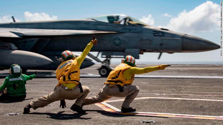 Sailors signal an F/A-18E Super Hornet to launch from the flight deck of the USS Ronald Reagan during flight operations in the Indian Ocean.