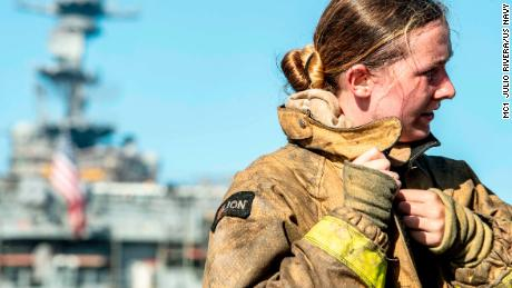 A sailor takes off her firefighting ensemble after combating a fire aboard the amphibious assault ship USS Bonhomme Richard.
