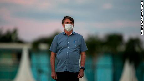 Brazilian President Jair Bolsonaro stands in front of the Alvorada Palace in Brasilia, where he has been in quarantine since testing positive for coronavirus.