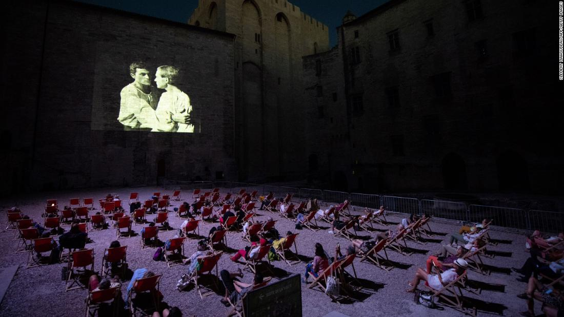 People watch a video projection in Avignon, France, on July 18. Since the Avignon Theatre Festival has been canceled because of the coronavirus pandemic, the festival's organization has been projecting plays that made its history.