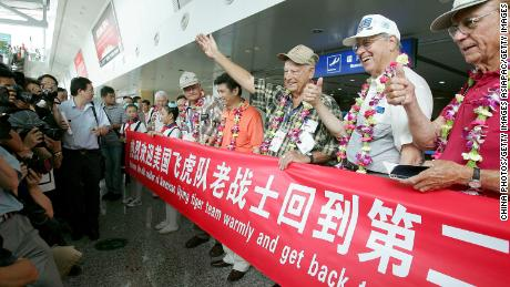 US World War II veterans, including former Flying Tigers, pose for pictures with a banner as a cheering crowd welcome them at the Chongqing Jiangbei Airport on August 18, 2005.