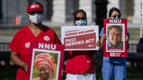 Nurses hold signs of nurses who've died from coronavirus at a public vigil in front of the US Capitol.