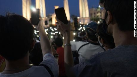 Protesters hold up their mobile phones during an anti-government demonstration at Democracy Monument in Bangkok on July 18.