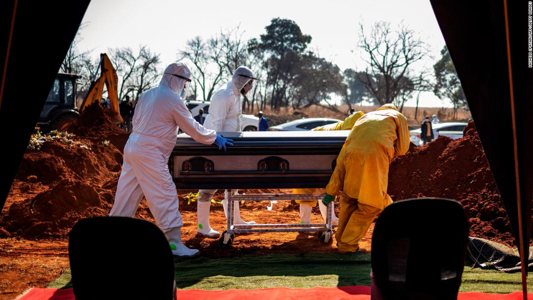 Undertakers push the casket of a coronavirus victim during a funeral in Soweto, South Africa, on July 21.