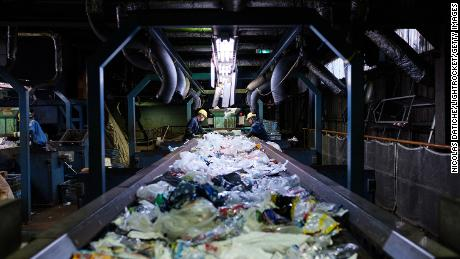 Workers sort disposable plastic waste on a conveyor at Ichikawa Kankyo Engineering recycle center. Tokyo's Katsushika city office brings some 10 tons of plastic recyclable resources to the recycling facility daily.